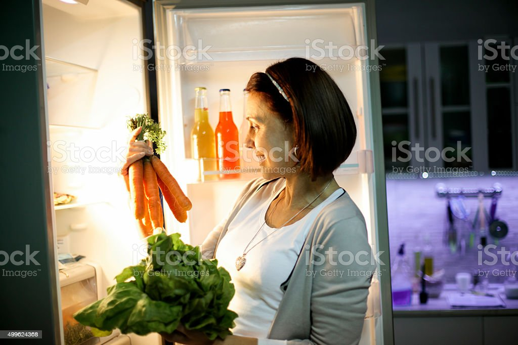 Woman in the dark at open refrigerator stock photo
