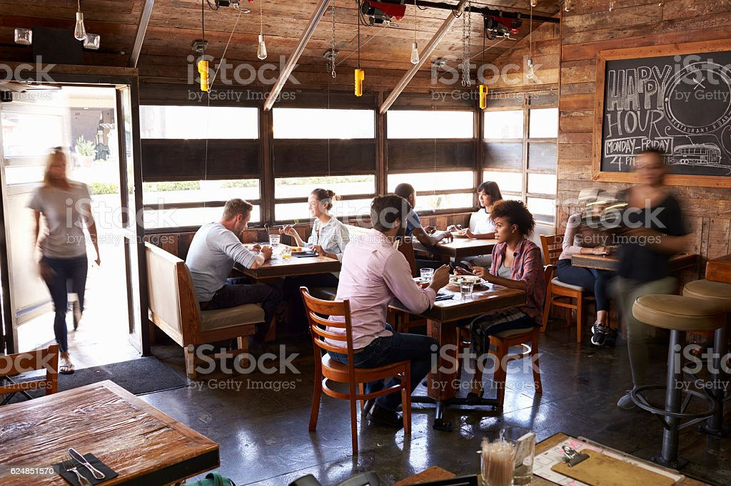 Woman in the doorway of a busy restaurant at lunchtime stock photo