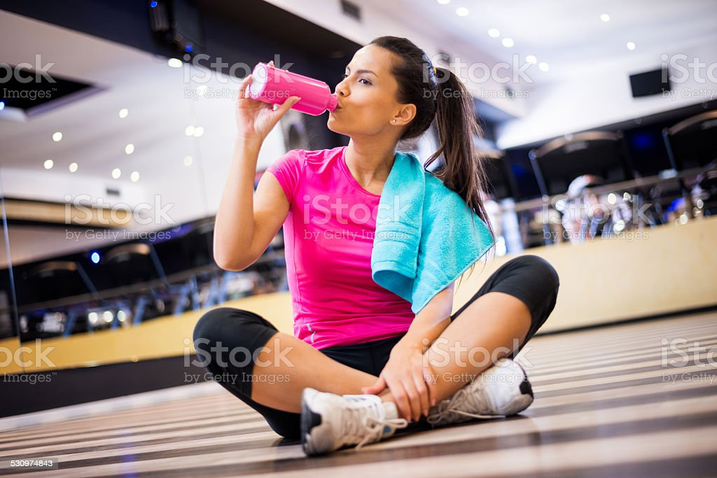 Woman in the gym hydrating stock photo