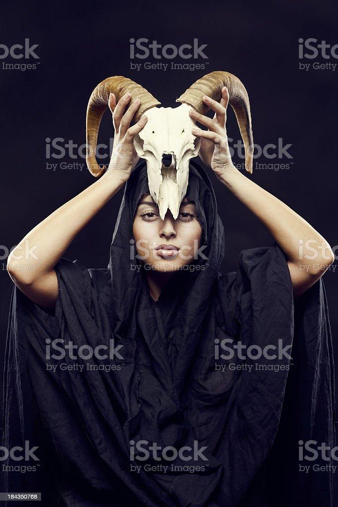woman in the hood raises sheep's skull over his head stock photo