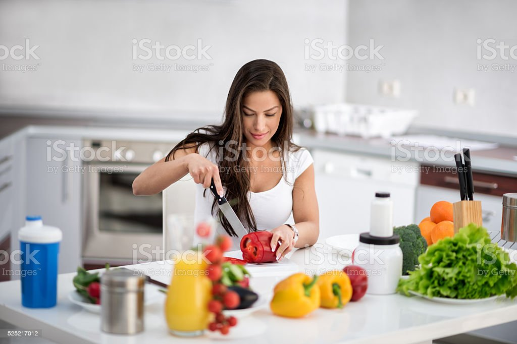 Woman in the kitchen cutting bell pepper stock photo