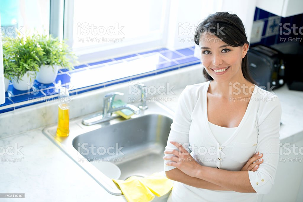 Woman in the kitchen washing dishes stock photo