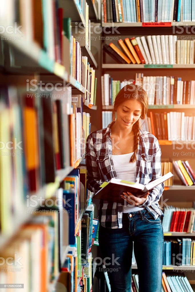 Woman in the library reading book. stock photo
