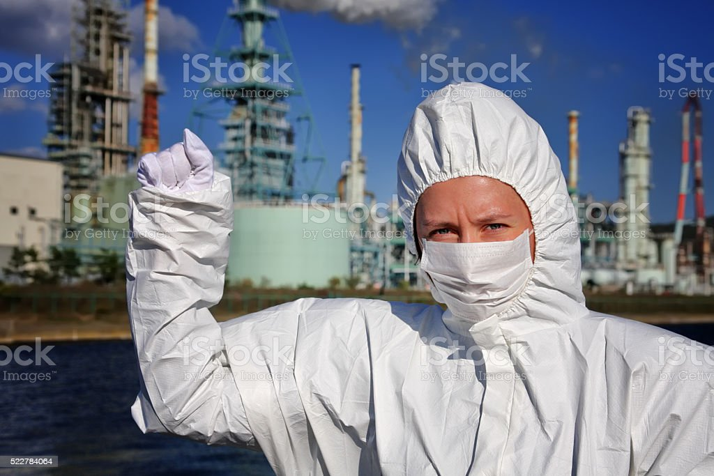 Woman in the mask clenches her fist with factory behind stock photo