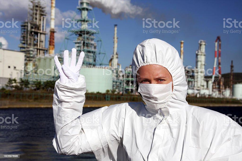Frau in der Maske zeigt Nummer vier mit Fabrik hinter Lizenzfreies stock-foto