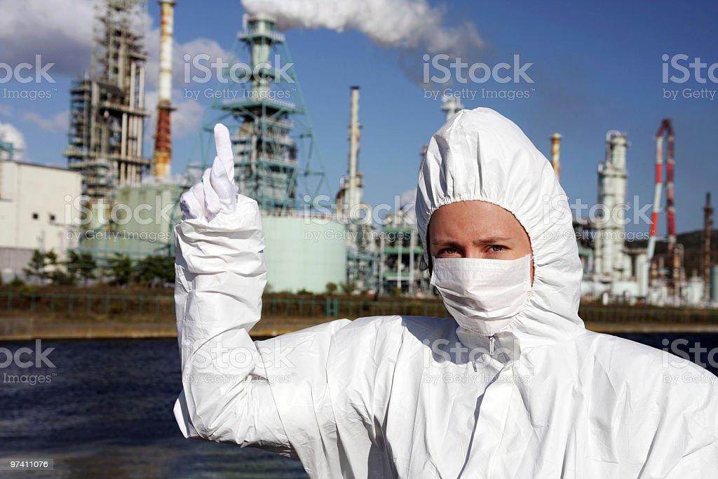 Frau in der Maske zeigt Nummer eins mit Fabrik hinter Lizenzfreies stock-foto