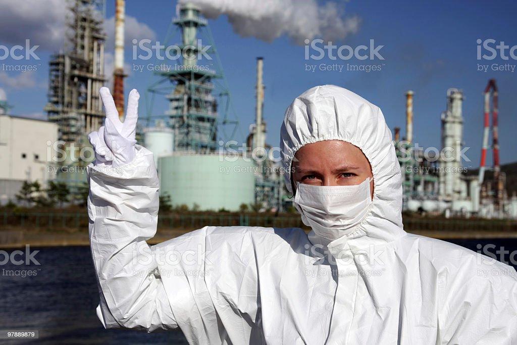 Frau in der Maske zeigt Nummer zwei mit Fabrik hinter Lizenzfreies stock-foto