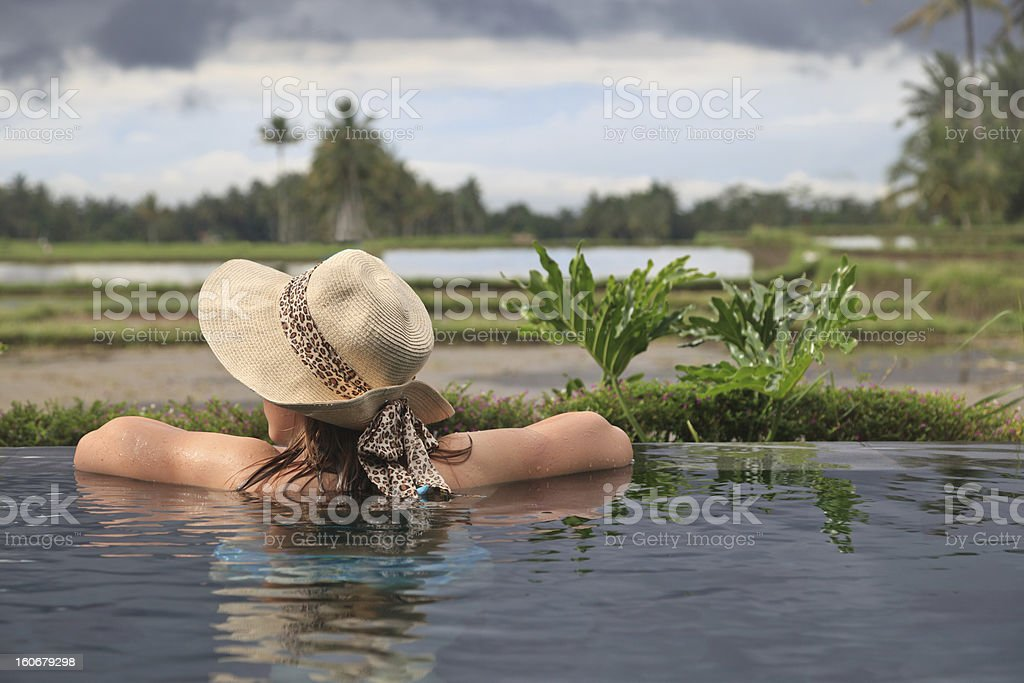 woman in the pool overlooking rice fields royalty-free stock photo