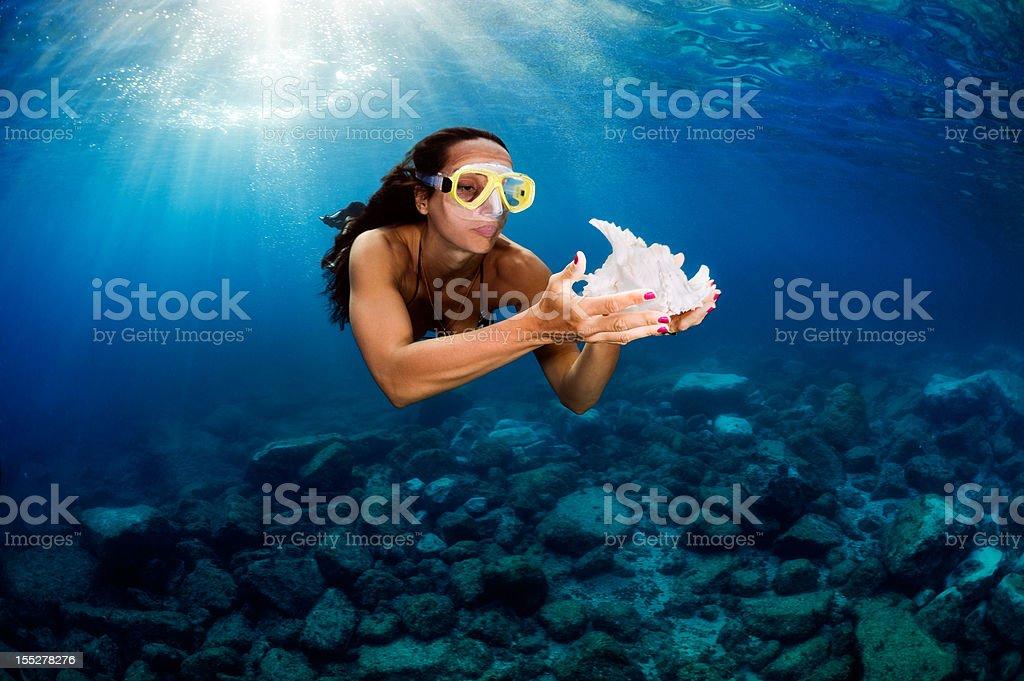 Woman in the sea holding a seashell royalty-free stock photo