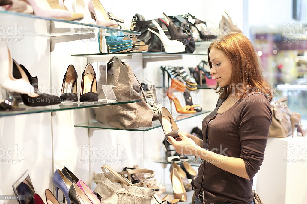 Woman in the shop to buy shoes royalty-free stock photo