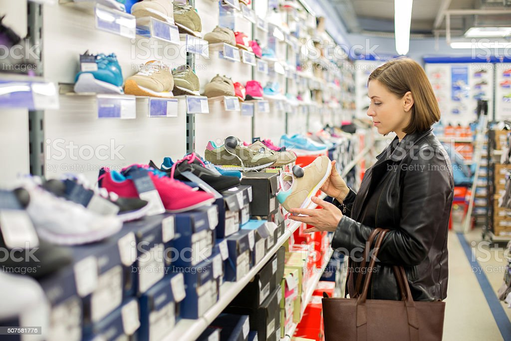 Woman in the shop to buy shoes stock photo