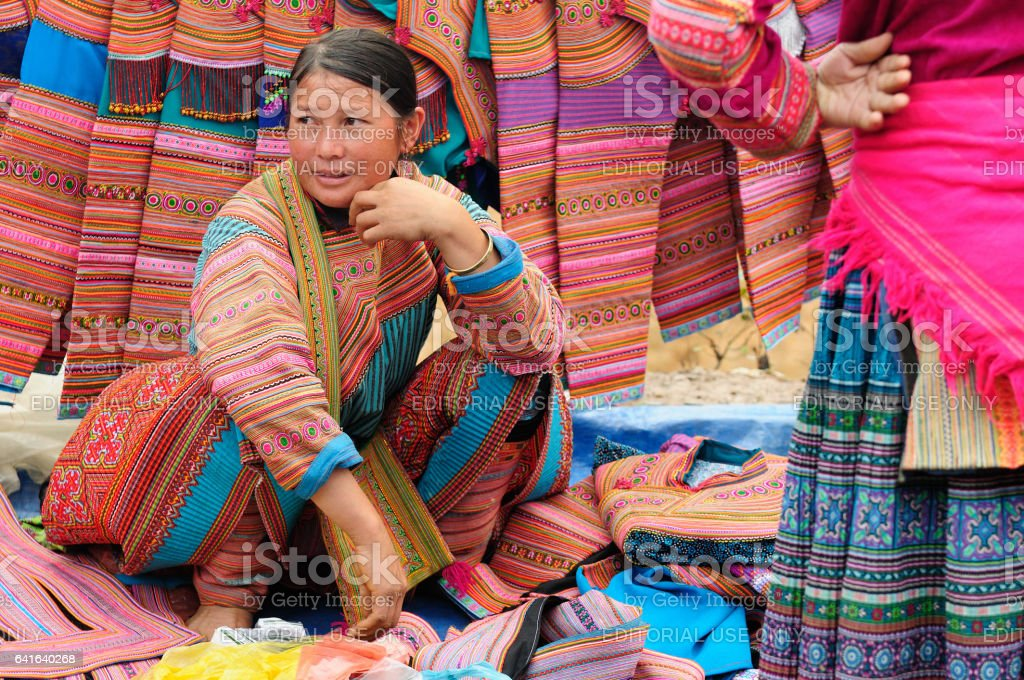 Woman in the traditional dress of Flower Homong selling traditional fabrics stock photo