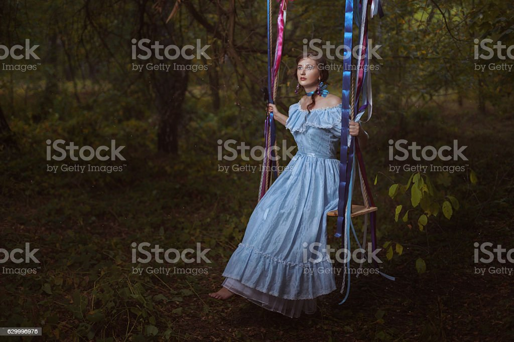 Woman in the woods on a swing. stock photo