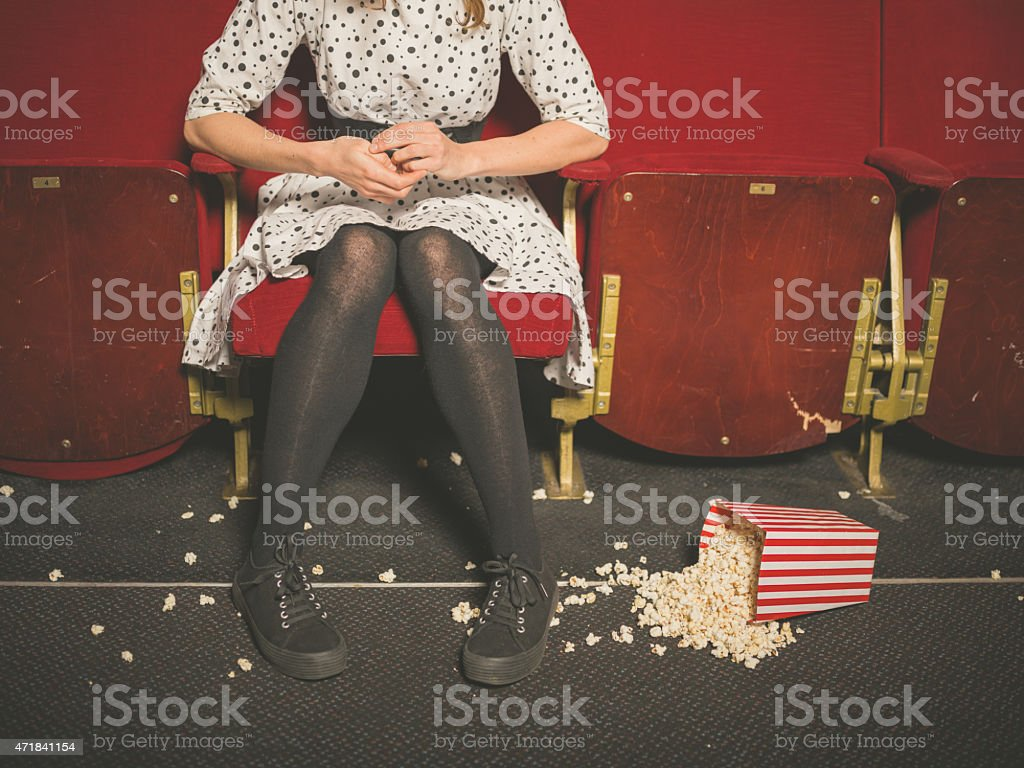 Woman in theater with popcorn on the floor stock photo