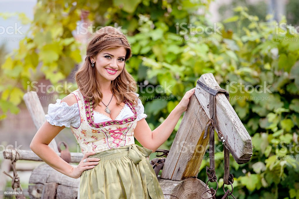 Woman in traditional bavarian dress sitting on wooden horse stock photo