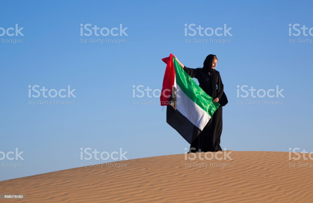 woman in traditional emirati dress holding a flag on UAE in a desert stock photo