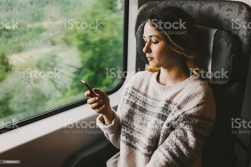 Woman in train with smartphone stock photo