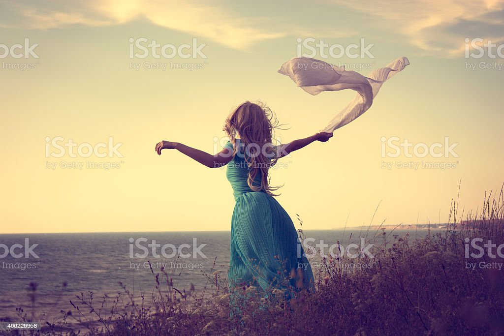 Woman in Turquoise Dress with Fabric at Sea stock photo