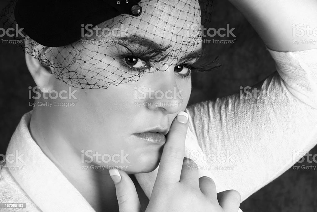 Woman in veiled hat touching face with pensive expression. royalty-free stock photo