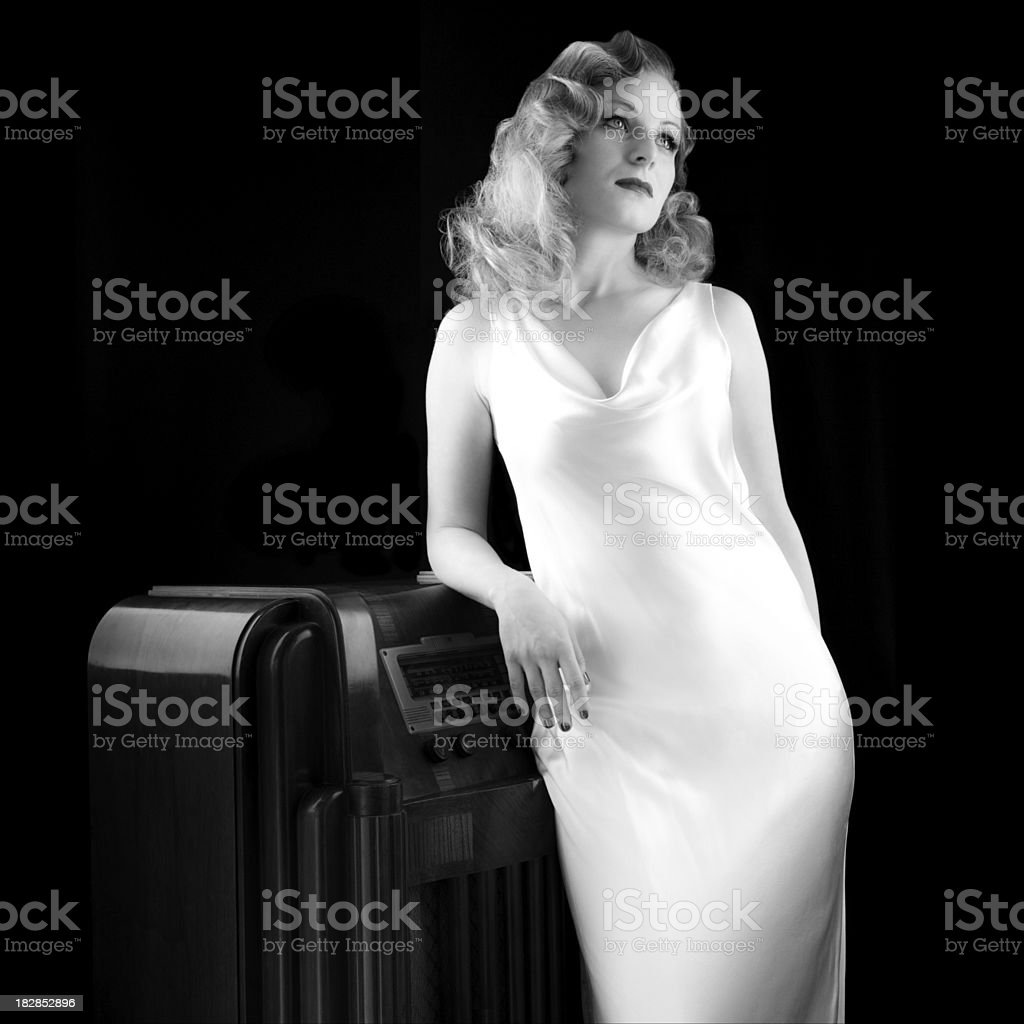 Woman in Vintage 1940's Attire Leans Against Old Radio. B&W. royalty-free stock photo