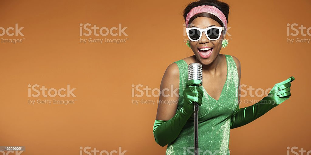 A woman in vintage attire singing soul funk in a microphone stock photo
