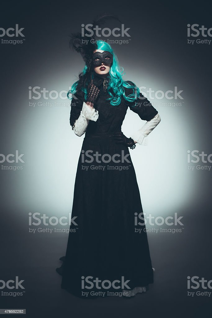 Woman in Vintage Gown with Dramatic Mask stock photo