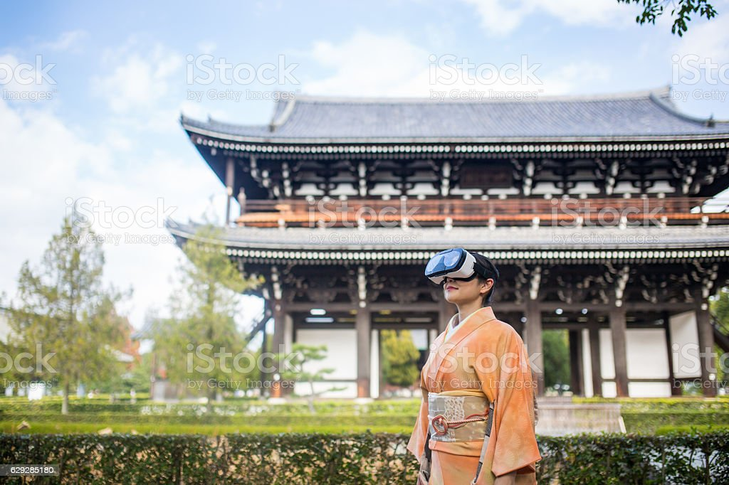 Woman in virtual reality headset surrounded by Japanese scenery stock photo