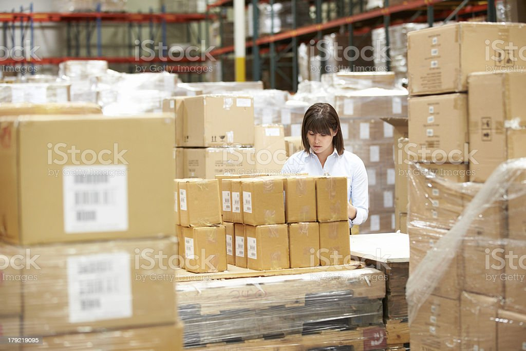 Woman in warehouse preparing packages for delivery royalty-free stock photo