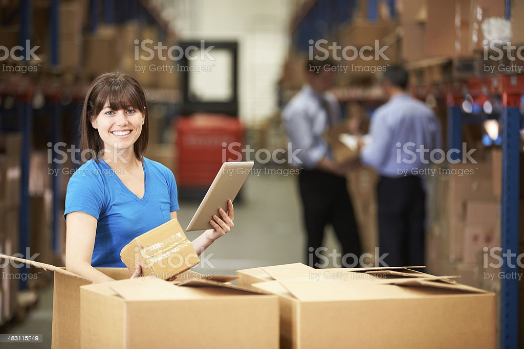 Woman in warehouse with boxes and digital tablet stock photo