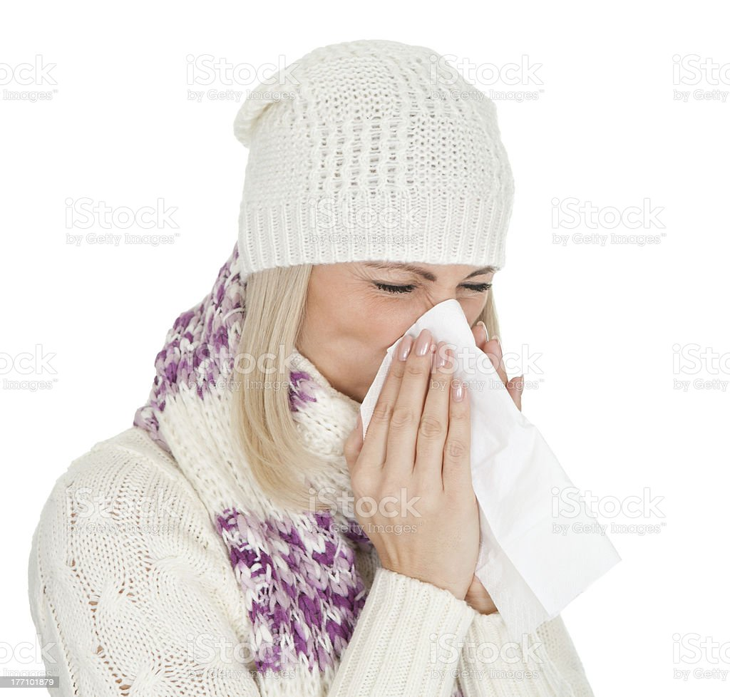Woman in warm winter clothing sneezing from cold royalty-free stock photo