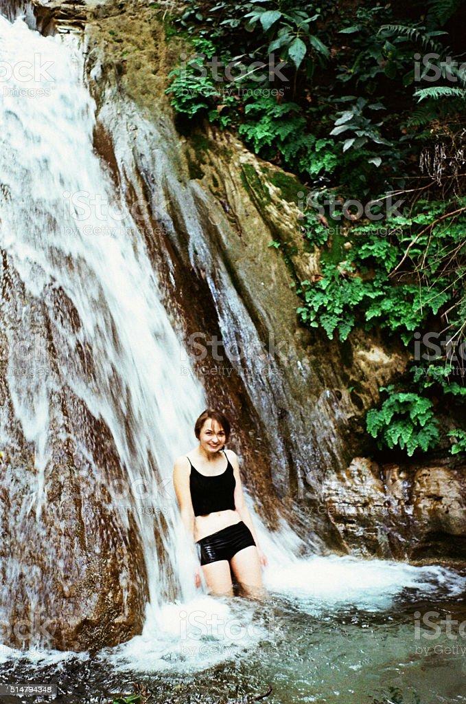 Woman in waterfall stock photo