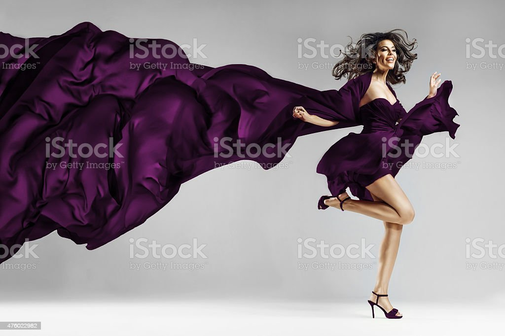 Woman in  waving dress with flying fabric stock photo