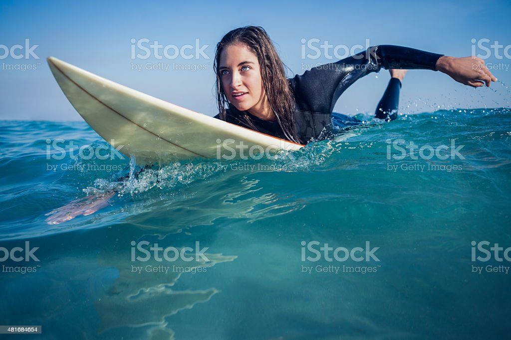 woman in wetsuit with a surfboard stock photo