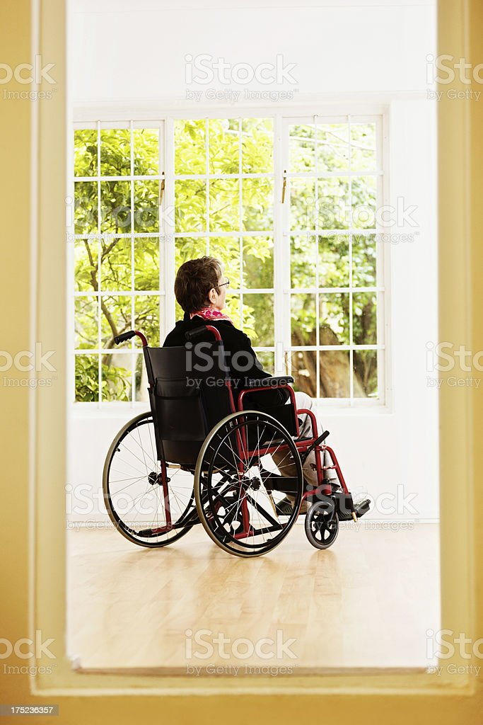 Woman in wheelchair can see but not reach spring garden stock photo