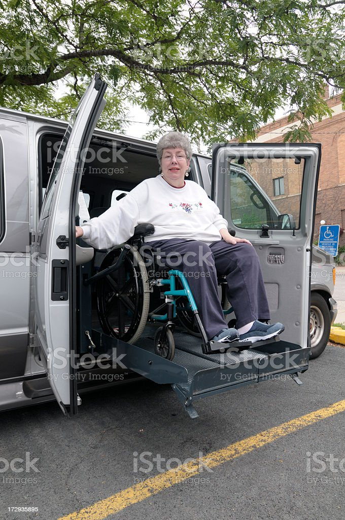 Woman in wheelchair on van lift being lowered to the street stock photo