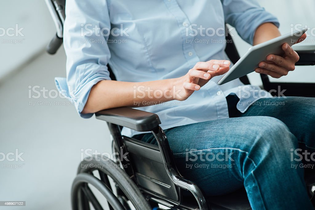 Woman in wheelchair using a tablet stock photo