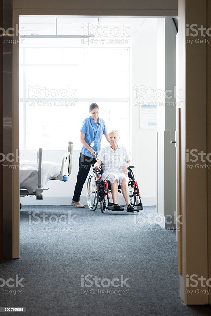 Woman in wheelchair with nurse, view through open door stock photo