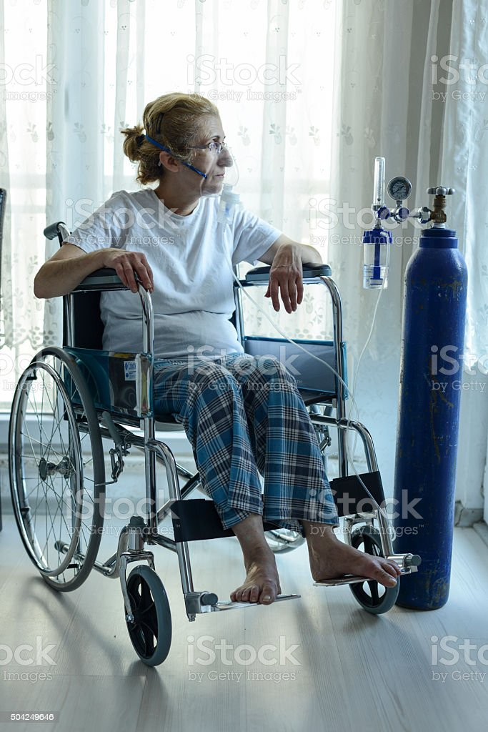 Woman In Wheelchair With Oxygen Mask stock photo
