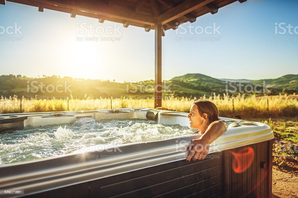 Woman in whirlpool jacuzzi during spa treatment stock photo