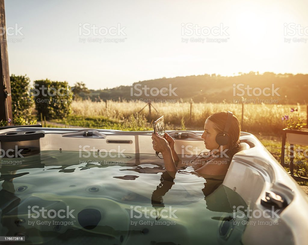 Woman in whirlpool jacuzzi with digital tablet stock photo