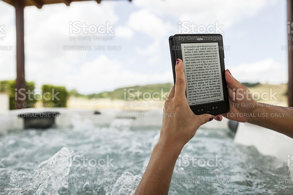Woman in whirlpool jacuzzi with Kindle royalty-free stock photo