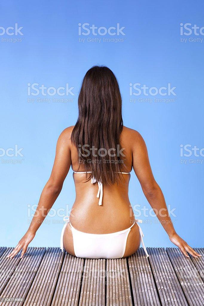 Woman in white bikini sat on a pier royalty-free stock photo