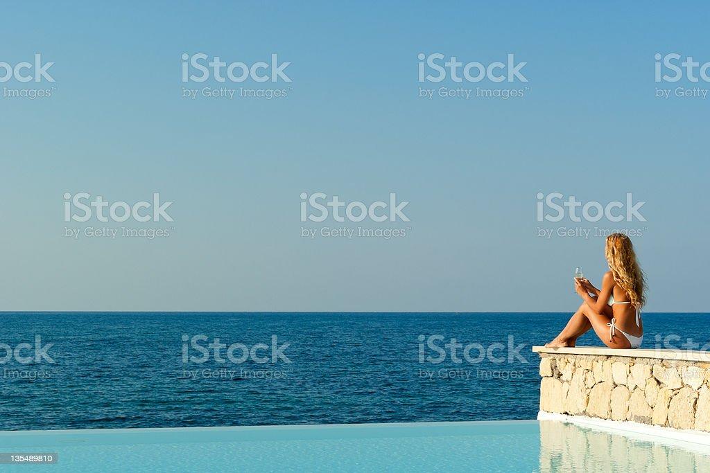 Woman in white bikini sitting near infinity pool stock photo
