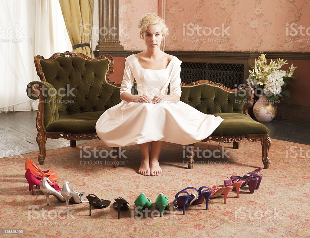 Woman in white dress encircled by pairs of shoes stock photo