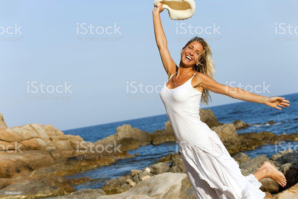 Femme en robe blanche sauter sur la plage photo libre de droits