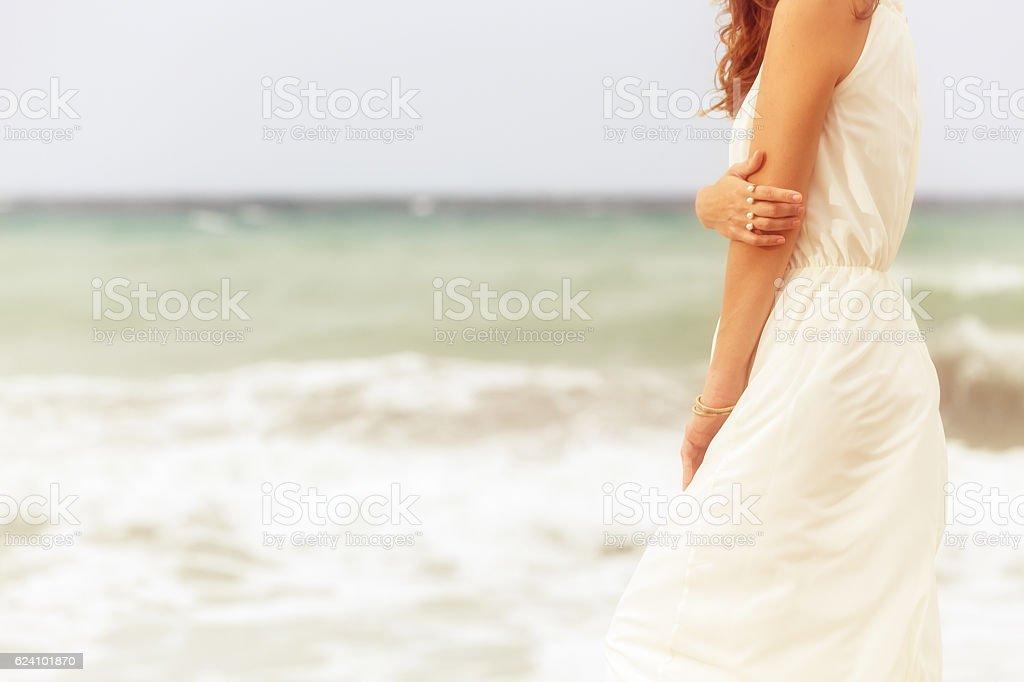 woman in white dress on beach stock photo
