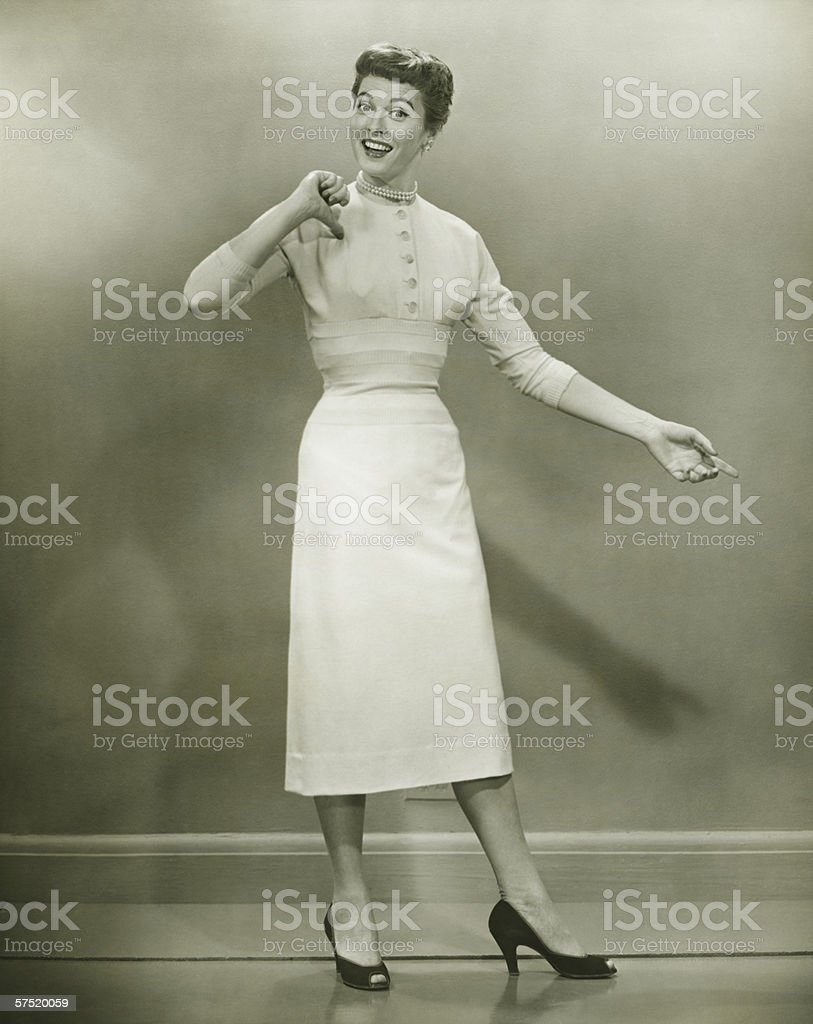 Woman in white dress pointing to herself in studio, (B&W), portrait stock photo