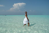 woman in white dress walking  in transparent water