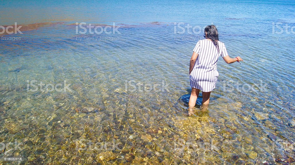 Woman in white dress walking on the beach stock photo
