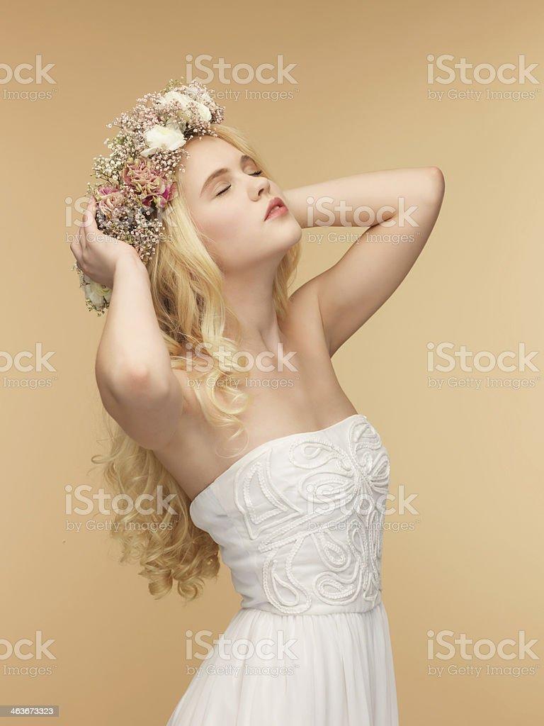 woman in white dress wearing wreath of flowers stock photo